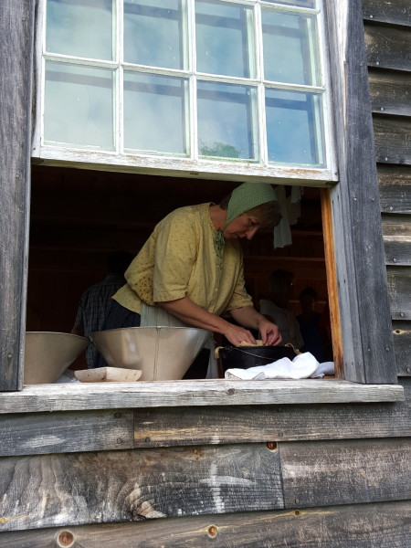 An historical re-enactor making bread at the Village Historique Acadien