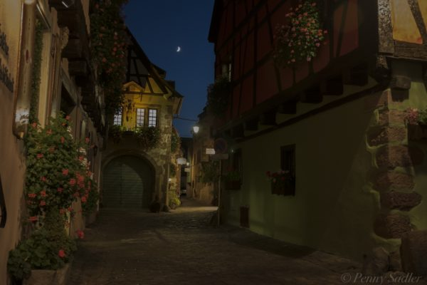 Pretty side street with a bright moonlight visible in Riquewihr, Alsace