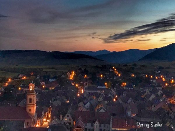 Village at night with lights on in Alsace